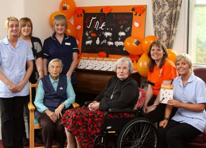 Residents and staff at Buxton's Pavilion Care Home meet chair of the Buxton Festival Fringe, Stephanie Billen (in orange), to unveil a special wall display made by the residents to celebrate the Fringe. Pictured clockwise from top left: care assistant Julie Standidge, activity co-ordinator Amy Moss, home manager Jayne Davidson-Pinder, Stephanie Billen, care assistant Leah Kenny, resident Sandra Shilton (in wheelchair) and resident Ivy Tongue. (Credit: Jason Chadwick. By kind permission of Buxton Advertiser)