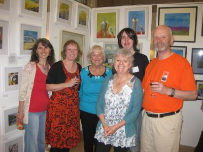 Fringe Vice Chair, Maria Carnegie, Fringe Secretary Pam Mason, Green Man volunteers Wendy Sheville and Charles Denton (behind), The Green Man's Events Manager, Caroline Small, and Fringe Chair Keith Savage against a backdrop of pictures at The Green Man Gallery.