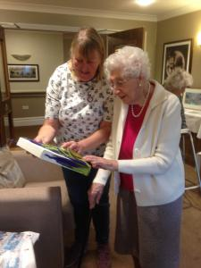 Cathey from Buxton Art Trail shows a resident from Haddon Hall Care Home a piece of artwork from the Trail contributed by artist Fiona Jubb.